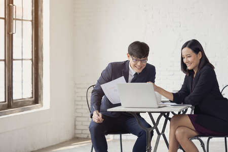 business man and woman sit at ther table looking at computer laptop 版權商用圖片