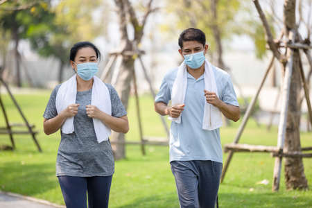 Senior couple in cooper wearing protective mask, Just keep going Stay active, stay well 版權商用圖片