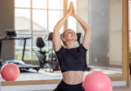 Woman in an athletic look with aerobic exercise stretching loose, Young sporty woman stretching sit in lotus pose doing yoga exercise breathing fresh air meditating in gym lit with sunlight at gym. 版權商用圖片