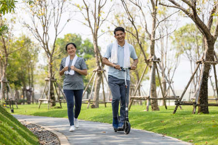 Couple workout and exercise with scooter together outdoor in park 版權商用圖片