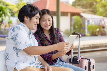 Young asian couple backpacker using tablet for find destination trip at railway station 版權商用圖片