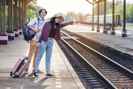 man & woman with backpack waiting for train at railway station. loving couple traveler travel together on holiday