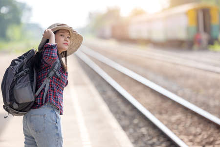 A young tourist girl with backpack waits for train on railway station for travel and journey
