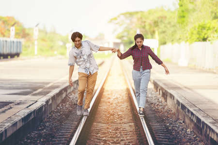 Young couple walking hand in hand on railway tracks, along railroad togethe