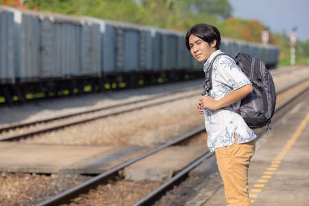 Young asian traveler with backpack in the railway, Backpack and hat at the train station with a traveler, Travel concept