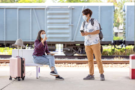 Young male traveler backpack with mask and mobile in hand asking way for help from woman sitting and pointing on stairs at subway, covid distance