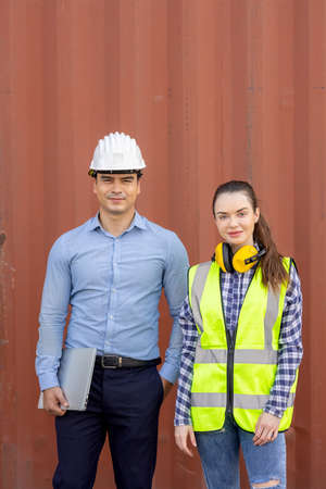 Confident engineers portrait in uniforms standing in front of the containers. Logistics and shipping. Professional occupation.