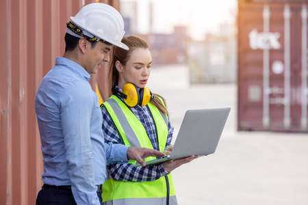 Two person foreman engineering helmet wear white safety are working computer pc notebook about import export investment technology digital at warehouse