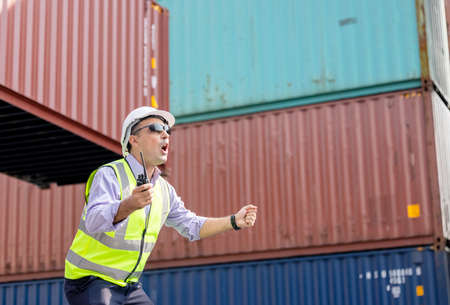 Man Using Walkie Talkie At Container Terminal, Industrial worker is controlling container loading 版權商用圖片