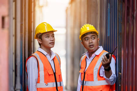 Two factory workers or engineers looking and pointing something in containers warehouse storage 版權商用圖片