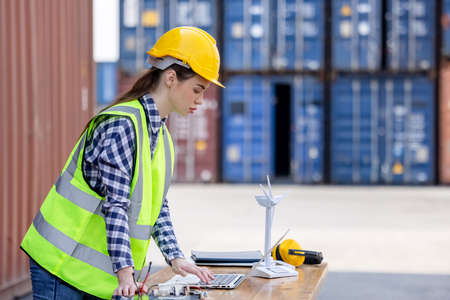 factory workers or engineers holding light bulb and using tablet computer with windmill model on solar panel,  work in containers warehouse storage 版權商用圖片