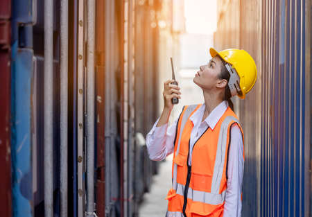 Portrait of Asian worker woman in safety uniform talking with walkie talkie to control work quality at container warehouse. working for logistic and shipping business.