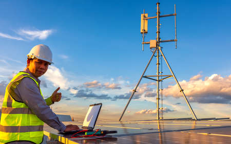Engineer using laptop at solar panels on rooftop at sunset sky, An engineer working at a photovoltaic farm. Eco technology for electric power