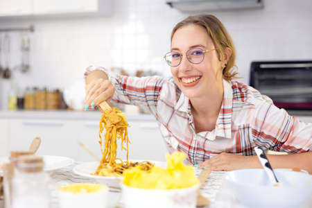 In the kitchen at home, a beautiful woman with a tablet prepares a pasta meal, and a lovely young woman eats pasta. 版權商用圖片