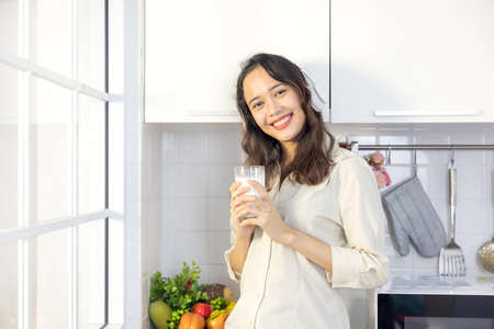 In a light modern kitchen, a beautiful woman drinks milk while listening to music. Before breakfast, she's having a good time and smiling.