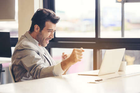 I finished the challenge! A very happy businessman is utilizing a laptop computer at the office. The idea of achieving success in business, at work, and in school. Man is a victorious individual. The concept of online betting.