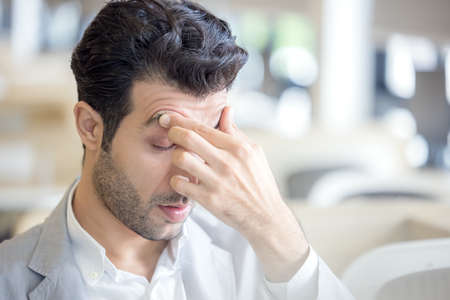 A tired young man's eyes are tired from computer work, while a stressed man suffers from a headache and poor vision. Use your laptop while sitting at an off-the-beaten-path table. 版權商用圖片