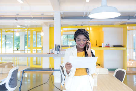 Portrait of a young black woman smiling while using her phone in a professional environment, either an African businessman or a student 版權商用圖片