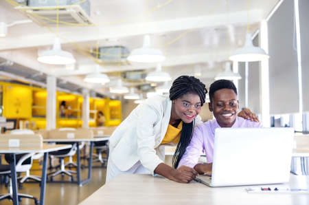 Portrait of a youthful black woman and guy smiling in a working environment with notebooks, African businessman or student