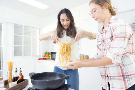 In the kitchen, two happy young twin sisters are preparing spaghetti for lunch.