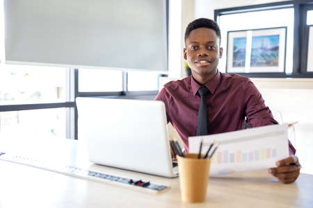 Portrait of a young black man using a laptop in a working environment, either an African businessman or a student. 版權商用圖片
