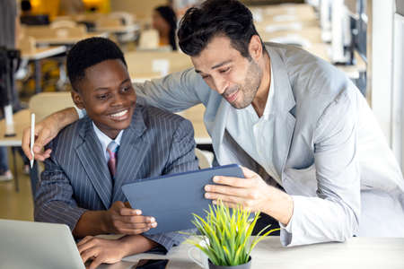 Using a computer tablet, focused black and white partners debate a project. Two multiracial male business associates