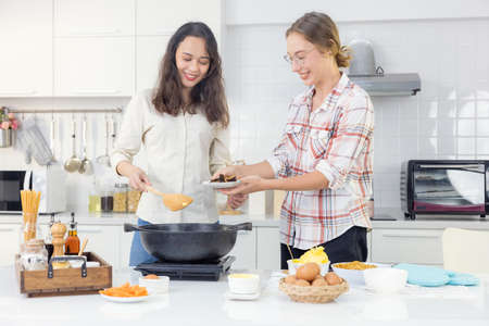 A joyful young lesbian pair in an apron cooks together in their home kitchen behind a wooden table with a frying pan and a spatula.