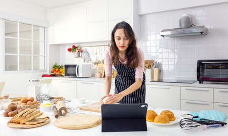 In her kitchen at home, a lovely young woman is taking an online cooking class on a tablet computer. 版權商用圖片