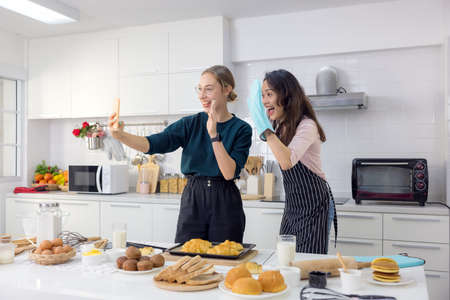 Two female pals are having fun while taking a selfie breakfast in the kitchen.