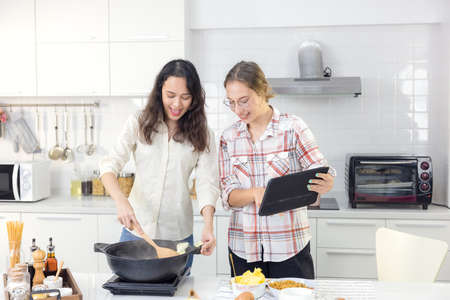 While cooking meals in the kitchen, a happy couple uses a smart tablet to look up a recipe online.