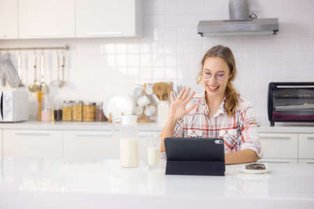 In a modern kitchen, a gorgeous young woman uses a digital tablet while eating a healthy breakfast.
