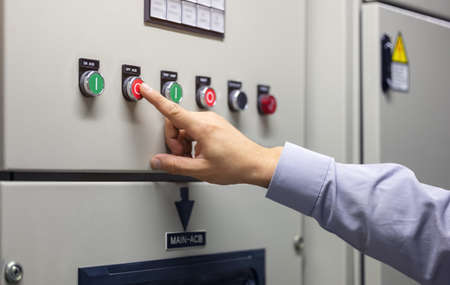 Working in the System Control Center room to show various information for data analysis in the industry, one hand operates the system control button of colors switch auto system.