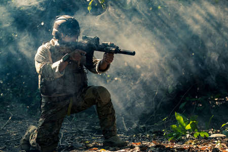 At a natural background, an army soldier in combat uniforms with an assault rifle or gun.