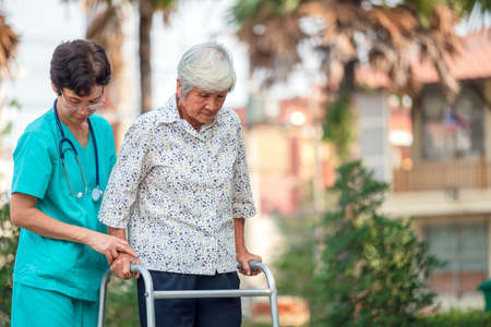 Assistance and care from a doctor Asian senior or elderly old lady woman patient in a nursing hospital ward, seated in a wheelchair: healthy robust medical idea