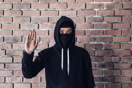 Over a brick wall, a hacker wears a black overcoat. 免版税图像