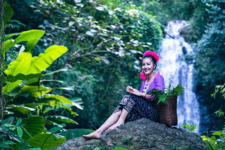 At a river waterfall in the Thai countryside, a young woman wears a flower crown on a rock.