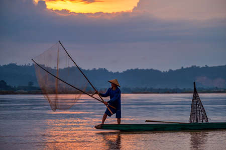 In the early morning before sunrise, an Asian fisherman on a wooden boat casts a net for catching freshwater fish in a natural river.
