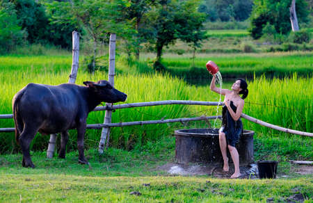At the countryside, a rural girl is taking a shower from a traditional groundwater source.