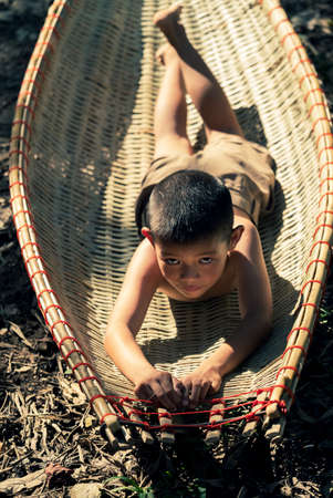In the Thai countryside, a young farmer is seen playing on the ground in a farmland.