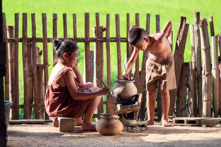 Asian children, a boy and a girl, are cooking in the kitchen of a Thai country house, where they live in the countryside. 免版税图像