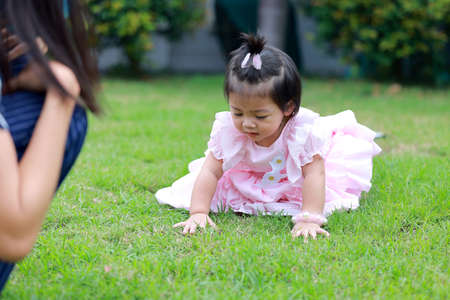 Sitting on the green grass, a lovely little girl wears pink fashionable clothing. 免版税图像