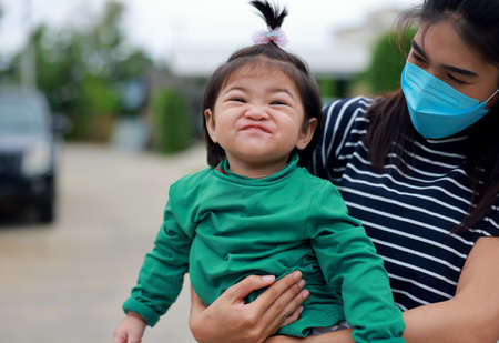 Portrait of a sweet tiny baby girl and her mother. Smile of a lovely young lady. a contented family 免版税图像