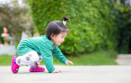 A lovely tiny baby girl is crawling in this portrait. Exercise is good for your health if you have a happy family. 免版税图像