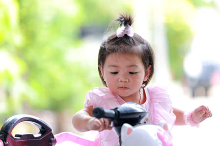 Face of a little girl riding a bicycle, Portrait of an adorable little Thai girl riding a bike in the outdoors.