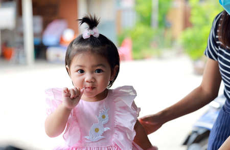 Young Thai girl with sugar and a sweet expression. A young girl eats candy. 免版税图像