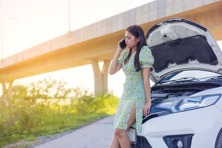 While looking at a broken down car on the street, a young woman is on her phone.Call an auto repair using a mobile phone when the car is broken.