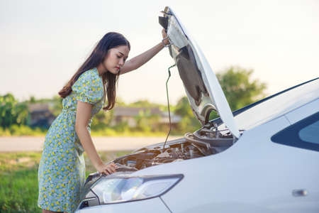 Aside from the portrait of a young attractive woman with a broken car, Asian women have a broken road. Check the engine by opening the hood.