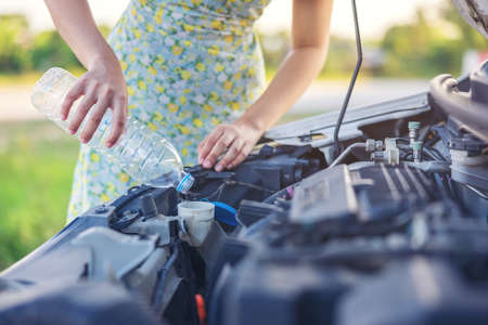 Fixing Her Broken Down Car, a young woman pours a water for washing glasses into her car.