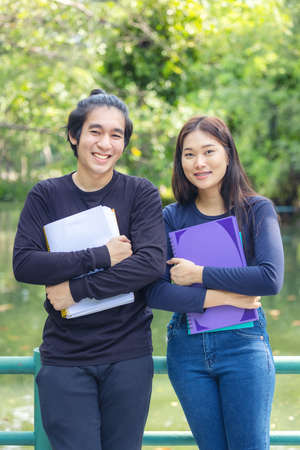 A gorgeous couple of students stands in a university campus park with exercise books and books in their hands, taking a break together.