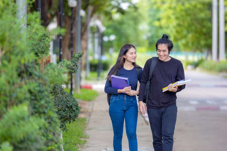 A young college student pair on their way to class. They are taking a walk around the university campus while reading a book. Autumn is a beautiful season. 免版税图像